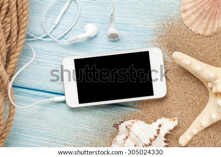 Smartphone on wood and sea sand with starfish and shells. Top view with copy space   - stock photo