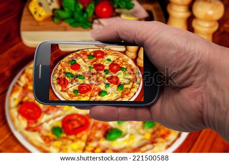 Smartphone shot food.Italian traditional  pizza with cheese and tomato