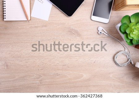 smartphone, tablet and office supplies on wooden background - stock photo