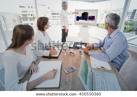 Smartphone, tablet computer and laptop against business people listening to colleagues presentation - stock photo