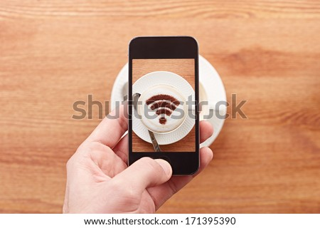 Smartphone taking photograph of free wifi sign on a latte coffe in a bar - stock photo