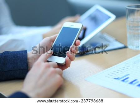 Smartphone, touchpad handheld in closeup, colleagues working in background.  - stock photo