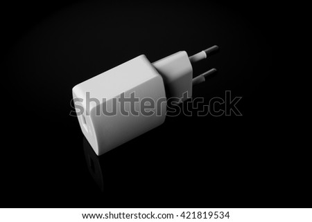 Smartphone white charger on black bacground, european type, top side view.