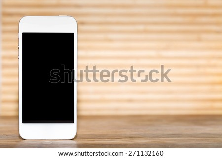 smartphone with a blank screen on a wooden table with a blurred background - stock photo