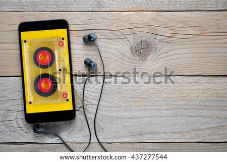 Smartphone with audio cassette image on display and headphones - stock photo