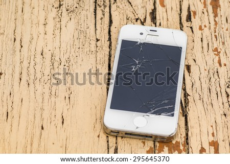 Smartphone with badly broken screen against rusty wooden background - stock photo