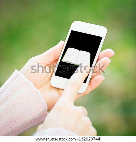 Smartphone with book in woman hands against green spring background - stock photo