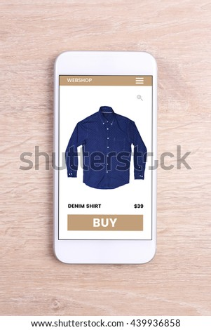 Smartphone with ecommerce screen website on wooden background  - stock photo