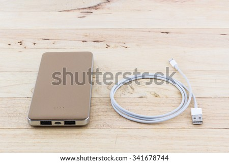 Smartphone with golden power bank on wood desk. - stock photo