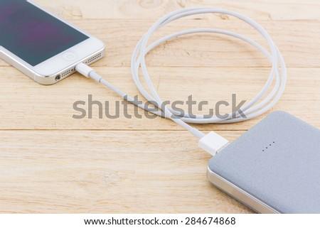 Smartphone with grey powerbank on wood desk.  - stock photo