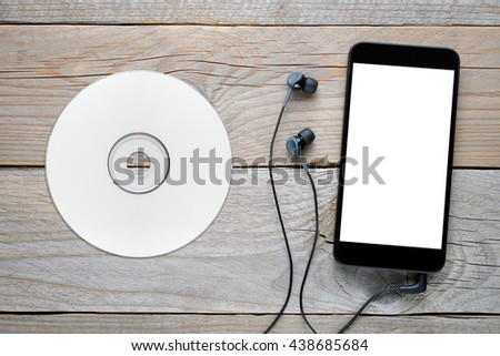 Smartphone with headphones and CD on wooden table - stock photo