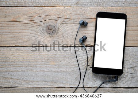 Smartphone with headphones on wooden background