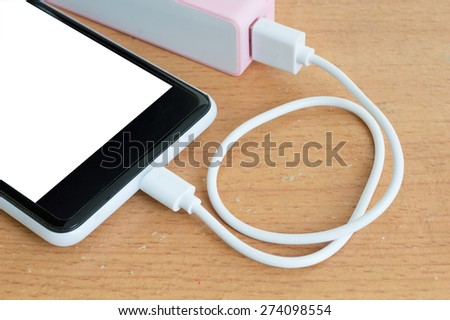 Smartphone with pink powerbank on wood desk  - stock photo