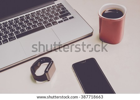 smartphone with smartwatch and laptop on the desk