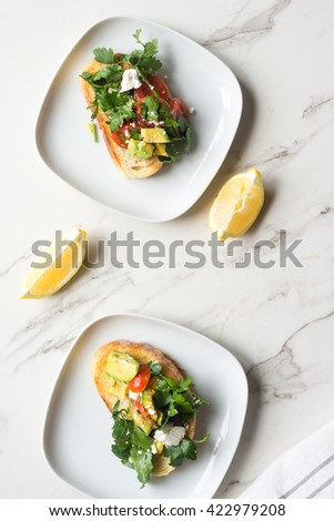 smashed avo on toast for breakfast, with feta, tomato, parsely,  - stock photo