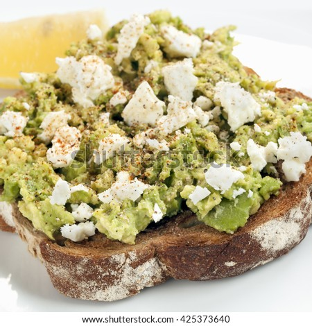 Smashed avocado and feta cheese on Toast.  With spices and lemon - stock photo