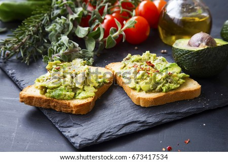Smashed avocado on toast, tasty healthy appetizers with cherry tomatoes and herbs, olive oil