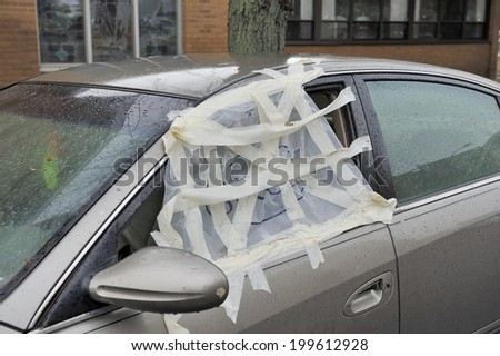 Smashed car window and temporary repaired with a plastic hide