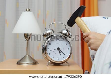 Smashing Alarm Clock with Hammer - stock photo