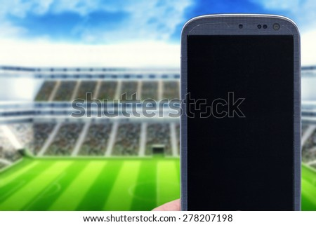 Smatrphone at stadium. Idea of taking shots, accessing apps, Internet, blogs and others related to soccer, footbal and other sports. The blur image is generated computer image of a stadium. - stock photo