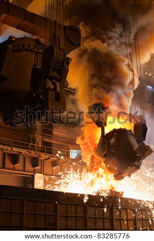 Smelting orange metal in a metallurgical plant. Liquid iron from the ladle - stock photo