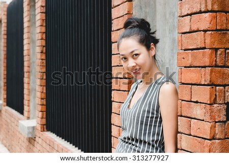 Smile Asian woman and brick wall.