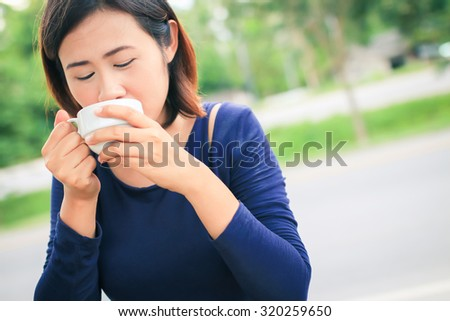 Smile asian woman holding cup of coffee with nature background.
