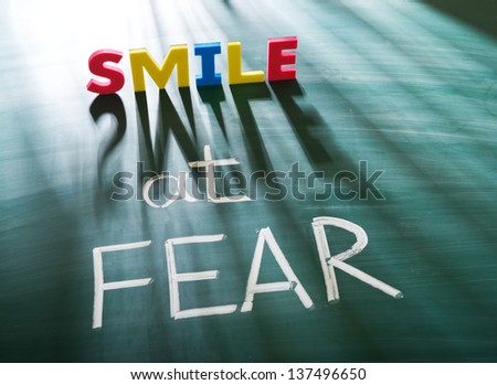 Smile at fear, conceptual words on blackboard