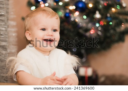 Smile baby boy near New Year tree - stock photo