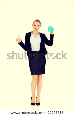 Smile business woman holding a paper house and show thumb up - stock photo