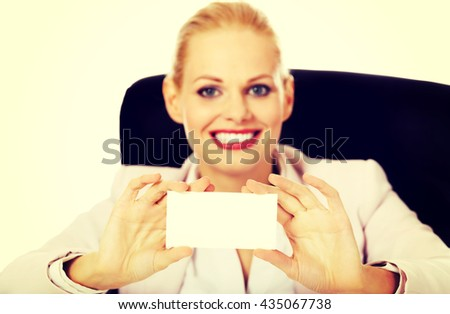Smile business woman sitting behind the desk and holding empty buisiness card - stock photo