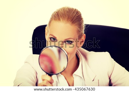 Smile business woman sitting behind the desk and looking into a magnifying glass - stock photo