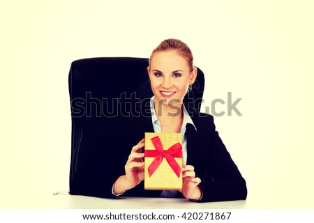 Smile business woman with gift box sitting behind the desk