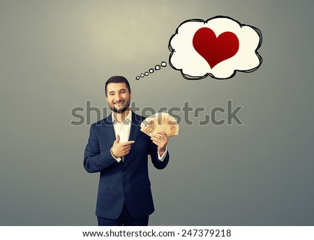 smile businessman pointing at paper money and thinking about love over grey background - stock photo