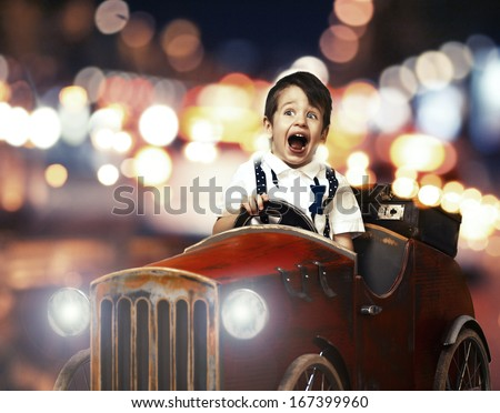 Smile child in wooden car in night on street - stock photo