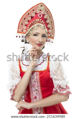 Smile coquettish young woman portrait  in russian traditional costume --  red sarafan and kokoshnik. Studio shot isolated on white. - stock photo
