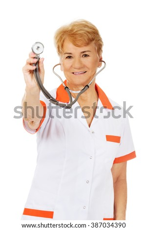 Smile elderly female doctor holding stethoscope - stock photo