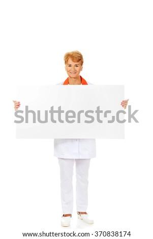 Smile elderly female  doctor or nurse holding blank banner - stock photo