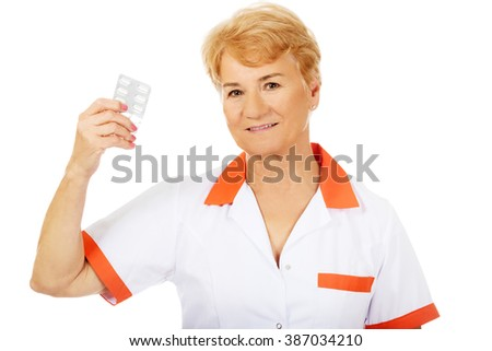 Smile elderly female doctor or nurse holds blister of pills - stock photo