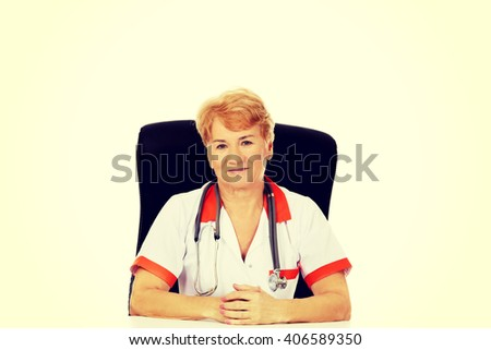 Smile elderly female doctor or nurse sitting behind the desk - stock photo