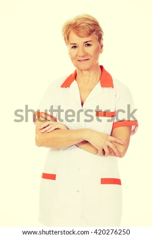Smile elderly female doctor or nurse with folded arms - stock photo