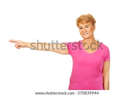 Smile elderly woman pointing for copyspace or something - stock photo