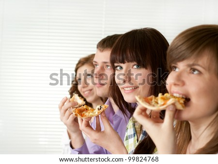 Smile funny Caucasian campaign of four people eating pizza on a light background - stock photo