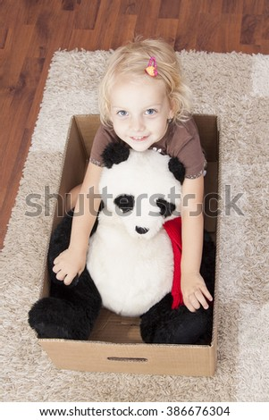 smile girl in a cardbox with her panda bear - ready to move - stock photo