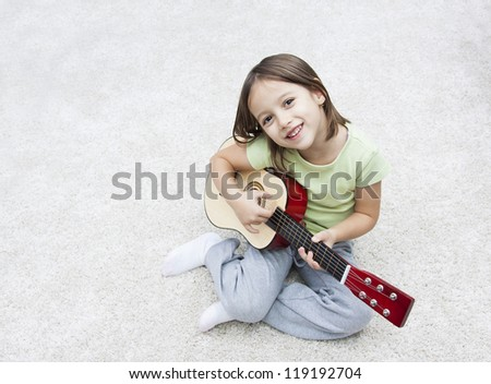 smile girl playing in guitar on the floor - stock photo