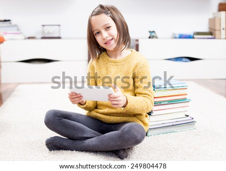 Smile girl playing on tablet - stock photo