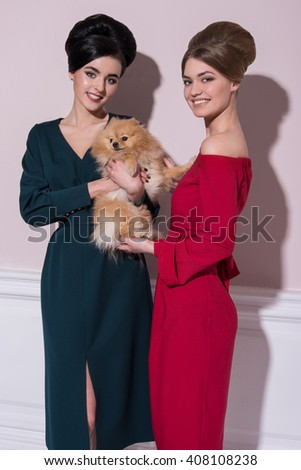 smile girlfriend, girlfriends, girls in ' 60s style, blonde and brunette, beautiful girls, cheerful girls, sunshine, girls walking laughing, girls with Spitz, girl with a dog, green dress, red dress - stock photo