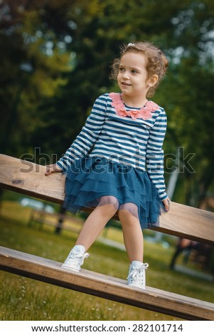 Smile happy little girl sitting on the bench in a park. Outsides - stock photo