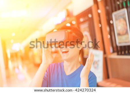 Smile happy man getting experience using VR-headset glasses of virtual reality - stock photo