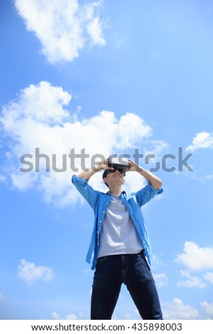 Smile happy man getting experience using VR-headset glasses of virtual reality with sky and cloud background